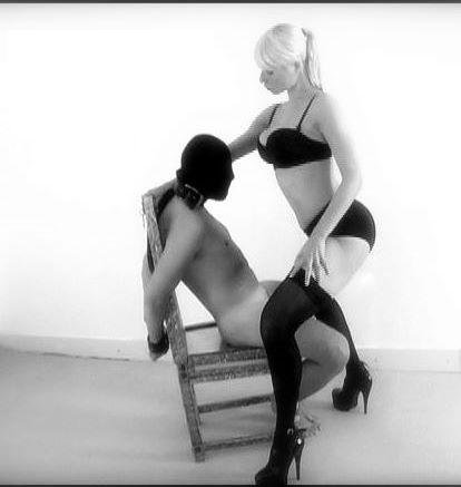 Dominate lady over a tied submissive call boy